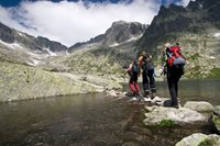 Three hikers cross crisp, clean water under beautiful sky and amongst majestic mountains