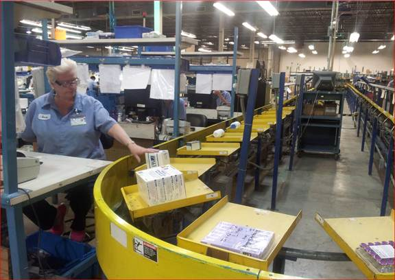 Guaranteed Returns employees use sorting machine to process pharmaceutical returns